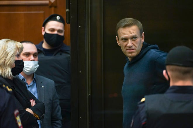 In this handout photo provided by Moscow City Court Russian opposition leader Alexei Navalny talks to his lawyers standing in the cage during a hearing to a motion from the Russian prison service to convert the suspended sentence of Navalny from the 2014 criminal conviction into a real prison term in the Moscow City Court in Moscow.