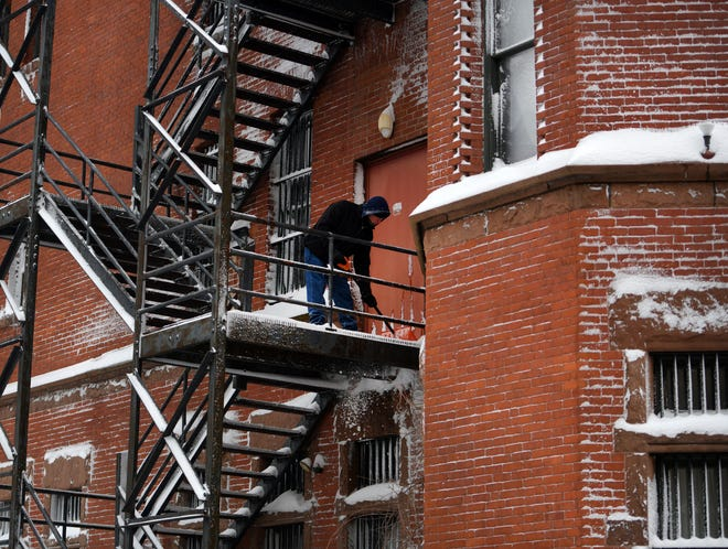 A man clears snow from the fire escape at Veterans Inc. on Grove Street.