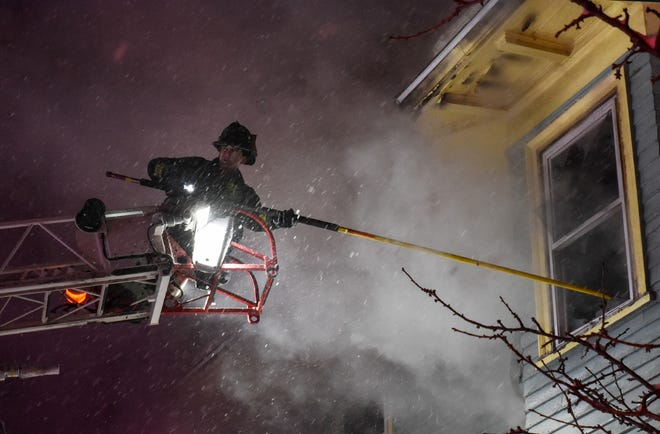 LEOMINSTER - Crews fight a 2-alarm fire at 291 Merriam Ave. during a snowstorm Monday night.