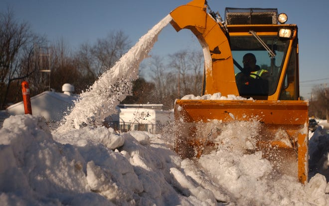 A Grafton Highway Department employee uses a giant snowblower to clear a sidewalk.