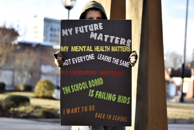 Miles Heinrich, 12, a Pine Forest Middle School student in Fayetteville, holds up a sign at a rally Tuesday, Feb. 2, 2021, calling for Cumberland County Schools to reopen.