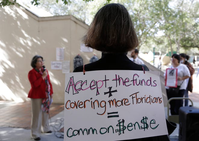 An activist wears a sign in support of Florida lawmakers expanding Medicaid during a protest in 2015 in Miami.
