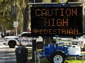 """A University of Florida police officer watches traffic pass a recently placed street warning sign that reads """"Caution High Pedestrian Traffic Area Ahead"""" on West University Avenue in Gainesville."""