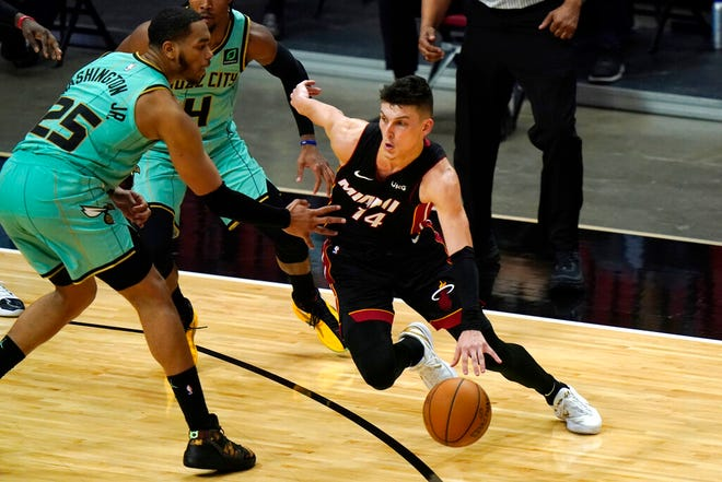 Miami Heat guard Tyler Herro (14) drives past Charlotte Hornets forward P.J. Washington (25) during the first half of an NBA basketball game, Monday, Feb. 1, 2021, in Miami. (AP Photo/Lynne Sladky)