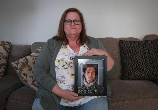 Renee Elings of Norwalk holds a photo of her son, Derick, who died of a drug overdose last June. His family says Derick had been sober for three years, but felt adrift without being able to attend AA and NA meetings because of the COVID-19 pandemic.