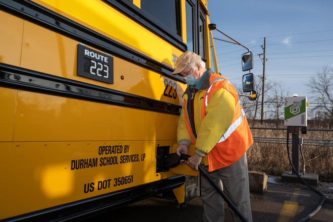 Bus driver Charlie Bogg charges an electric school bus in the parking lot of Ann Arbor's Pioneer High School.