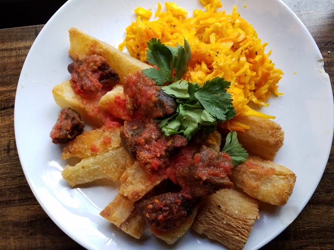 An order of fried yuca with pork and curtido slaw from Cinia's Salvadoran Kitchen. We took it out of the to-go box and put it on a plate with cilantro. Truth, there was a lot more pork but we snacked on it because it's that good. Sunday, Jan. 31, 2021.
