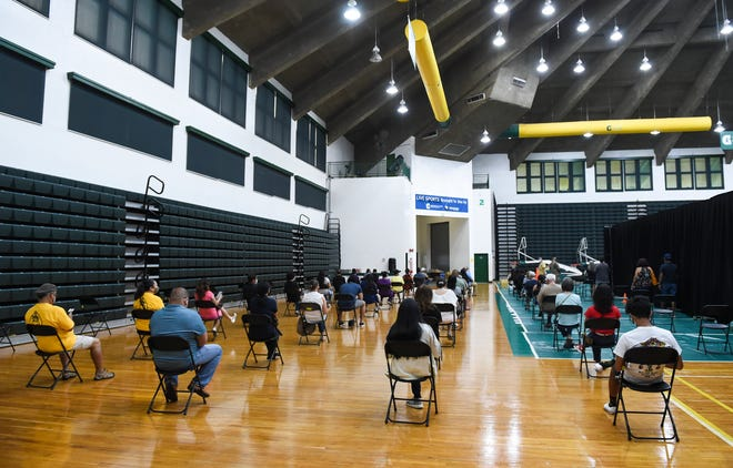 Patients wait to be called for a COVID-19 vaccination at the University of Guam Calvo Field House in Mangilao on Tuesday.