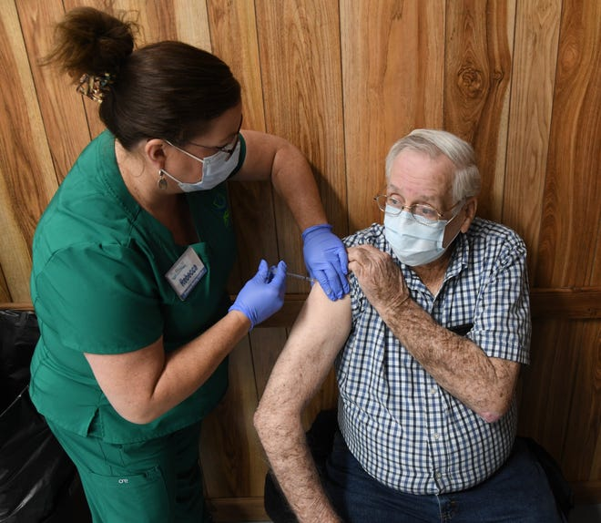 Frank Parker of Mountain Home receives the first dose of the COVID-19 vaccine from Arkansas State University-Mountain Home nursing student Rebecca Burns on Tuesday at the Baxter County Fairgrounds.