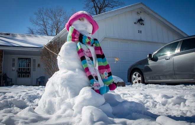 A snowman in the front yard of a house along West Charter Drive will likely melt away by Thursday as temperatures rise. Temps are expected to plummet to single digits by Sunday.
