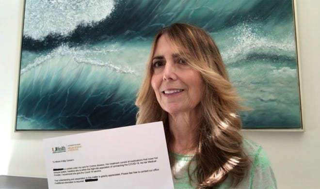 Jami Kaylor, 58, of Naples, holds her doctor's orders for a COVID-19 vaccination at her home, Tuesday, Feb. 2, 2021/