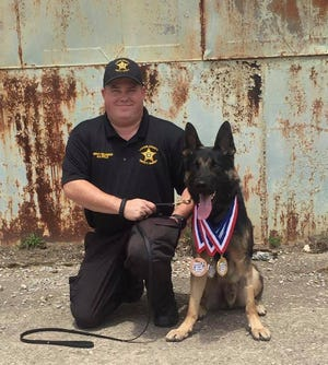 Licking County Deputy Dirk Williamson poses for a photo with K9 Apollo.