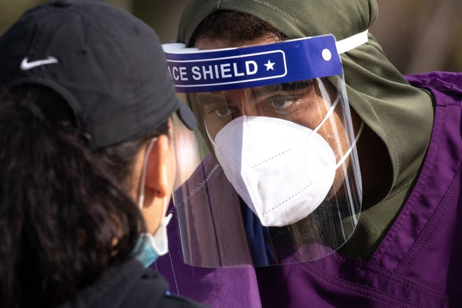 Dimitris Nesadurai (right), with Premier Lab Solutions, swabs a person getting tested on Feb. 2, 2021, during COVID-19 mobile testing at Cielito Park, 3402 W. Campbell Ave., Phoenix.