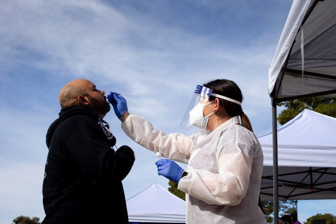 Manuel Renteria (left) is swabbed by Elise Chavez, with Premier Lab Solutions, on Feb. 2, 2021, during COVID-19 mobile testing at Cielito Park, 3402 W. Campbell Ave., Phoenix.
