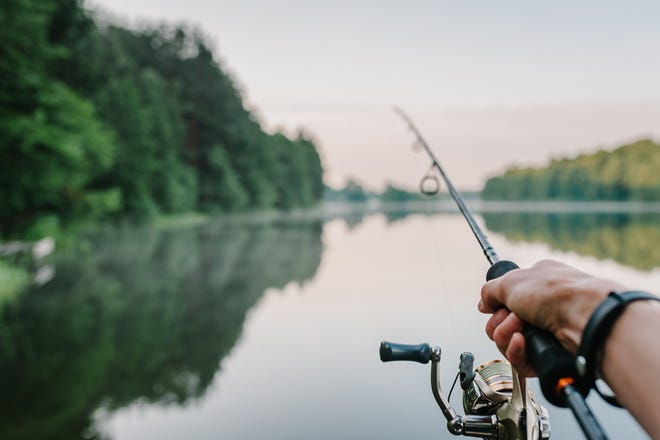 Fisherman with rod, spinning reel on the river bank.