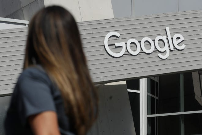 A woman walks below a Google sign on the campus in Mountain View, Calif.,  on Sept. 24, 2019.