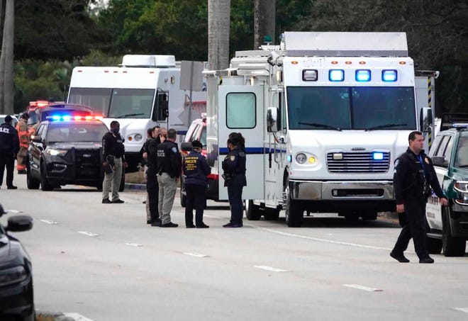 Law enforcement gather near the scene of a shooting in which FBI agents were killed and wounded in Sunrise, Fla., on Feb. 2.