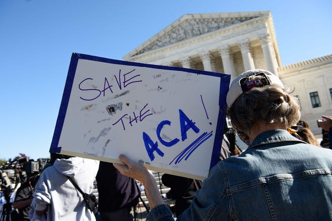 A  demonstrator held up a sign as the Supreme Court took up another challenge to the constitutionality of the Affordable Care Act on Nov. 10, 2020.