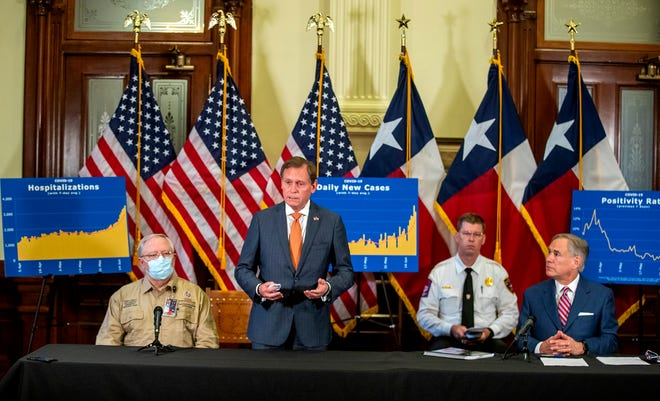 Dr. John Zerwas answers questions during an update on the state's pandemic response in June. Zerwas, a former lawmaker and the University of Texas System executive vice chancellor for health affairs, has served as a key medical adviser to Gov. Greg Abbott, seated to the far right, during the pandemic.