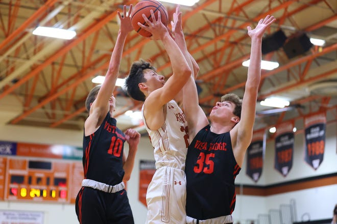 Westwood forward Eric Kipper drives through Vista Ridge defenders Braedyn Dawes, left, and Sam Scott in the first half of a District 26-6A game Tuesday at Westwood High School. Westwood went on to win the game over Vista Ridge by a final score of 80-54.