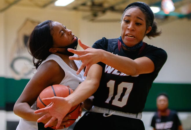 Connally Cougars forward Mariah Robinson, left, draws a traveling foul and collides into Weiss Wolves guard Treazure Sikes during the first period at the District 18-5A girls basketball game on Feb. 2 at Connally High School.