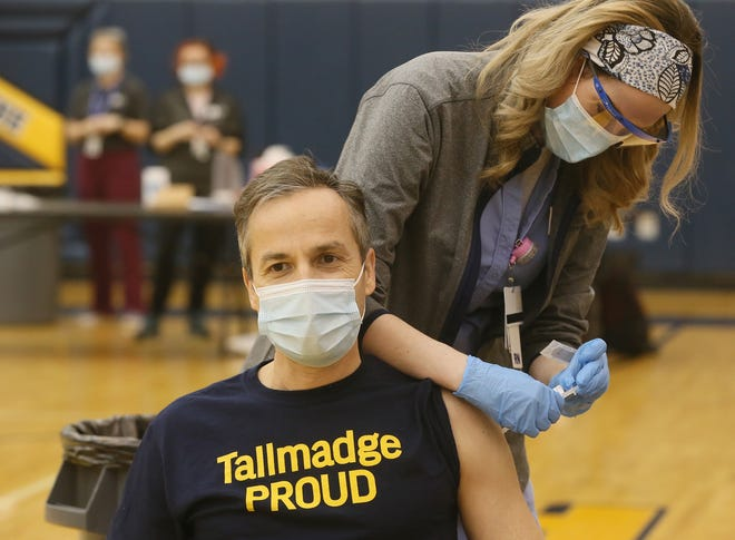 Tallmadge Schools Superintendent Steve Wood gets his first dose of the COVID-19 vaccine from Akron Children's Hospital RN Janelle Heiser on Feb. 3. Staff received the second dose Wednesday, and so many required additional recovery time that the district remained closed on Friday.