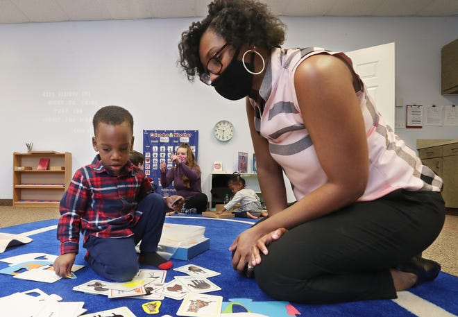 Lydia Stephens, owner/director of Montessori Life preschool, plays a matching game with her son and student Israel, 2, as teacher Brandi Crawford works with other students.