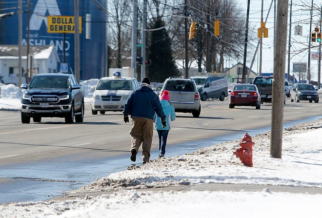 Two pedestrians walk south on Claremont Avenue in the road because the sidewalks were snow and ice covered on Wednesday, Feb. 3, 2021. TOM E. PUSKAR/TIMES-GAZETTE.COM