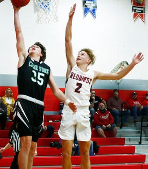 Clear Fork's Jared Scott (35) goes up for a layup as Loudonville's Kyle Maltarich (2) tries to block during high school boys basketball action Tuesday at Loudonville High School. The Colts defeated the Redbirds, 66-44.