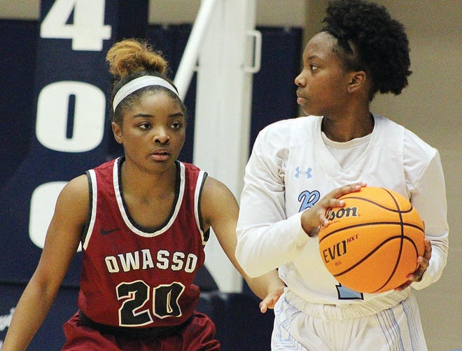 Bartlesville High point guard T'Keitha Valentine, right, studies her options during varsity girls basketball action Tuesday evening at home against the Owasso Lady Rams.