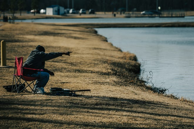 Chris Houston points to some fish jumping out of the water at Lee Lake in Bartlesville on Wednesday. Fish species at the lake include channel catfish, sunfish and largemouth bass.