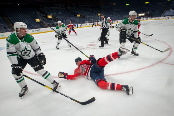 Columbus Blue Jackets right wing Patrik Laine (29) gets tripped by Dallas Stars defenseman Jamie Oleksiak (2) in front of Dallas Stars defenseman Miro Heiskanen (4) during the first period of the NHL hockey game at Nationwide Arena in Columbus on Tuesday, Feb. 2, 2021.