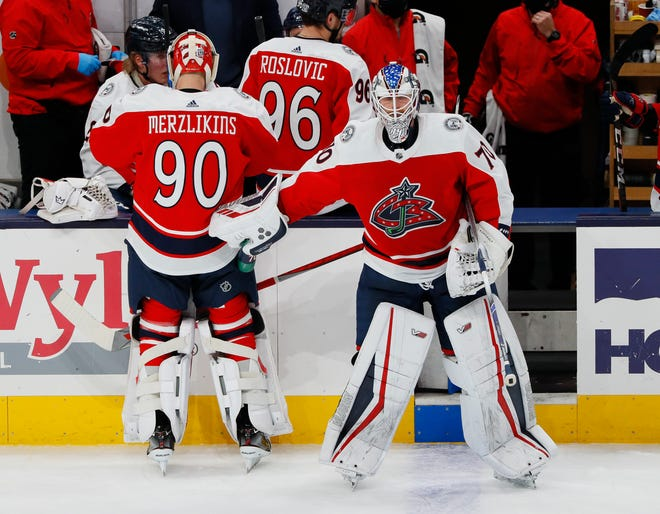 Columbus Blue Jackets goaltender Joonas Korpisalo (70) taps goaltender Elvis Merzlikins (90) as Merzlikins prepares to takes his spot in net during the second period of the NHL hockey game against the Dallas Stars at Nationwide Arena in Columbus on Tuesday, Feb. 2, 2021.