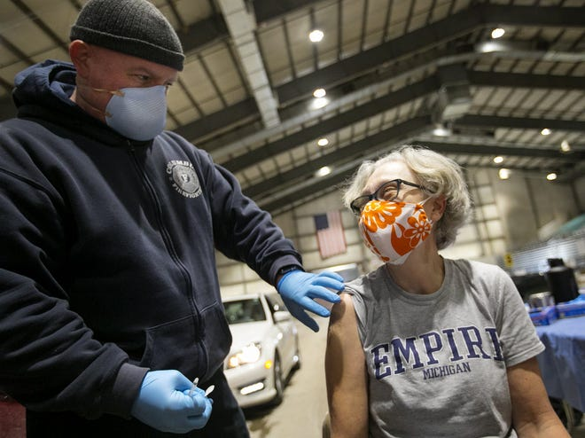 Elementary school teacher Ronda McIntyre from Indianola Informal K-8 receives her first dose of the COVID-19 vaccine, administered by Columbus firefighter Bill Toops at the Ohio Expo Center, Wednesday.
