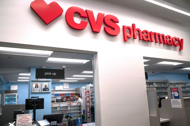 Pharmacist Evelyn Kim, wears a mask and gloves at the CVS pharmacy at a Target in Washington. The Biden administration will begin providing COVID-19 vaccines to U.S. pharmacies, including CVS, part of its plan to ramp up vaccinations as new and potentially more serious virus strains are starting to appear.