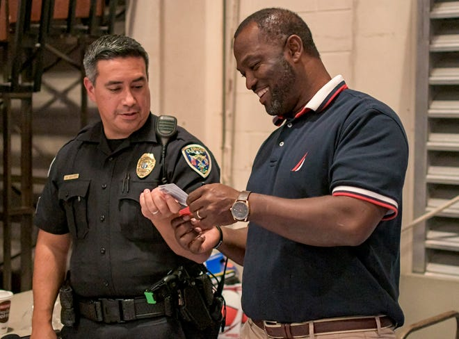 Sgt. Malcolm Draper of the Clermont Police Department gives a man a gift card during the 9th annual Battle of the Badges event at Clermont Elementary School on Dec. 13, 2019. (Paul Ryan/Correspondent)