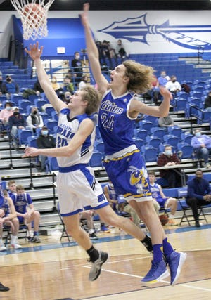 Buckeye Trail freshman Donovan Geiger (20) gets past East Canton's Caleb Schilling (24) for a layup during Friday night's IVC match-up in Old Washington. Geiger turned in a solid double-double effort for the Warriors with 11 points and 13 rebounds in a 48-41 Buckeye Trail victory.