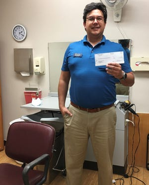 Ryan Salinas, SunPorch of Dodge City administrator, holds a check from the Community Foundation of Southwest Kansas. The funds are being used to update the hair salon at the short-term rehabilitation and long-term care residence.