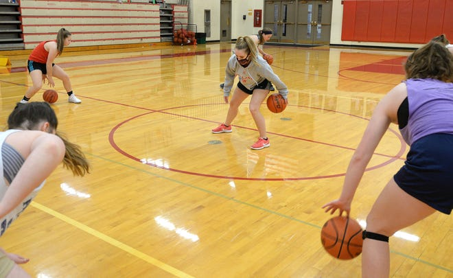 Katie Zewe, center, assistant coach of the General McLane girls basketball team, leads a ball-handling drill Wednesday at the school's gymnasium.