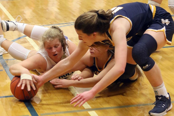 Holy Trinity's Brooke Mueller and Notre Dame's Megan Harrell and Gabby Deery scramble for a loose ball Tuesday at Shottenkirk Gymnasium in Fort Madison.