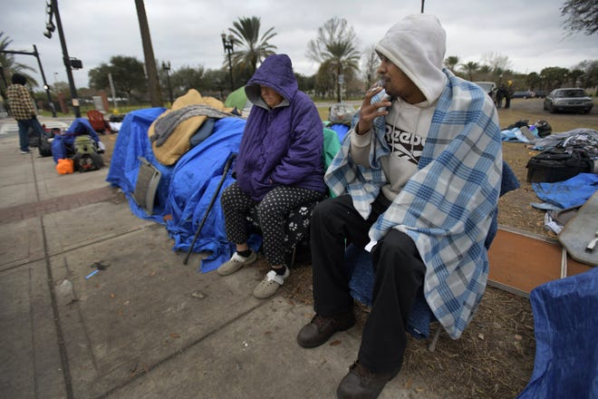 Katherine Creeg sits with David Collins as they shelter from the cold wind in the homeless camp along North Jefferson Street this week.  Homeless camps near downtown facilities that provide homeless services have been growing this winter.