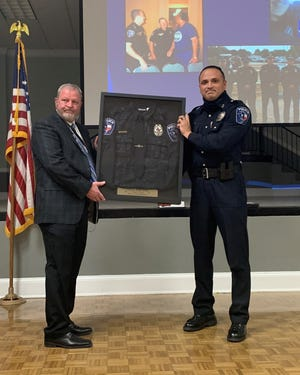 Sherman Police Office Mark Wood, left, and Police Chief Zachary Flores hold up a framed police uniform during Wood's retirement ceremony Tuesday.  Wood served for 23 years with the Sherman Police department, and served on the Critical Accident Investigation Team. Wood was recently recognized for his efforts to tightened Texas law with regard to protective order after discovering loopholes in the laws.
