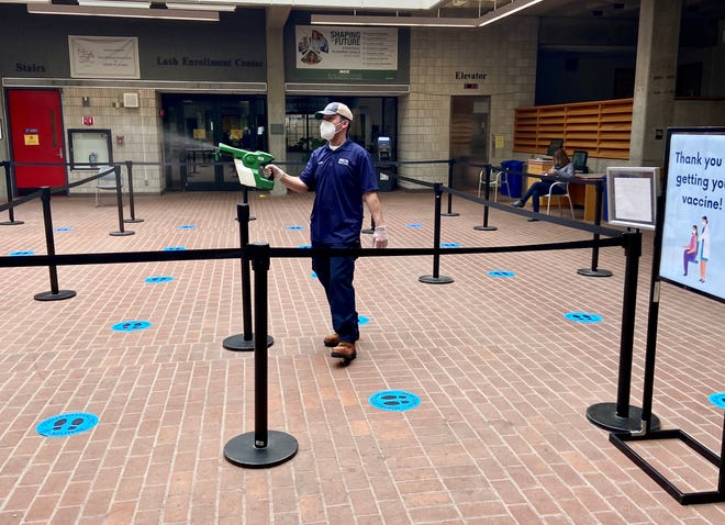 A Bristol Community College employee sanitizes the area just outside of the Building G cafeteria where people began getting their COVID vaccinations on in February 2021.
