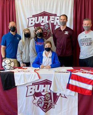 Buhler High School's Amaleigh Mattison, seen with her family and coaches, signs to continue her academic and soccer career at Hutchinson Community College.