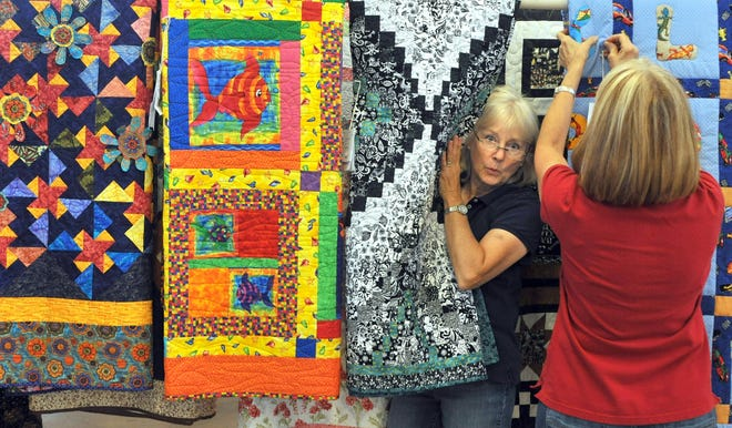 Diane Lingle pops from behind quilts on display in the Domestic Arts building next to Nancy Anderson Thursday, Sept. 6, 2012, at the Kansas State Fair in Hutchinson. The State Fair Board on Tuesday approved changes that will reduce the number of fair entries on display.