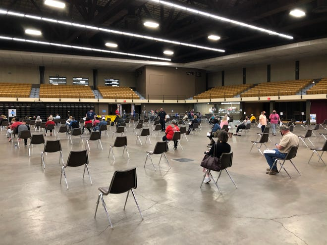 People waiting inside the Lubbock Memorial Civic Center on Tuesday after receiving a COVID vaccine.