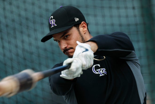 FILE - In this Friday, Sept. 27, 2019, file photo, Colorado Rockies third baseman Nolan Arenado warms up before a baseball game against the Milwaukee Brewers in Denver.