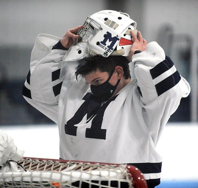 Medway High School junior goalie Evan Monaghan puts on his helmet just before the game against Dover-Sherborn/Weston, Feb. 3 at Pirelli Veterans Arena in Franklin.