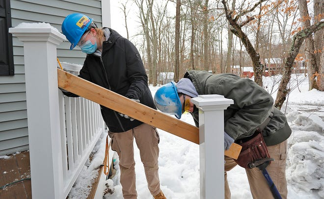 Megan Corrigan, of Milton, and Brandon McNichols, of Dedham, check the angle of a hand rail for the entry steps on a Canton home on Wednesday, Feb. 3, 2021. Students from the Blue Hills Regional Technical High Construction Technology program have spent three years building an addition onto a Canton home.
