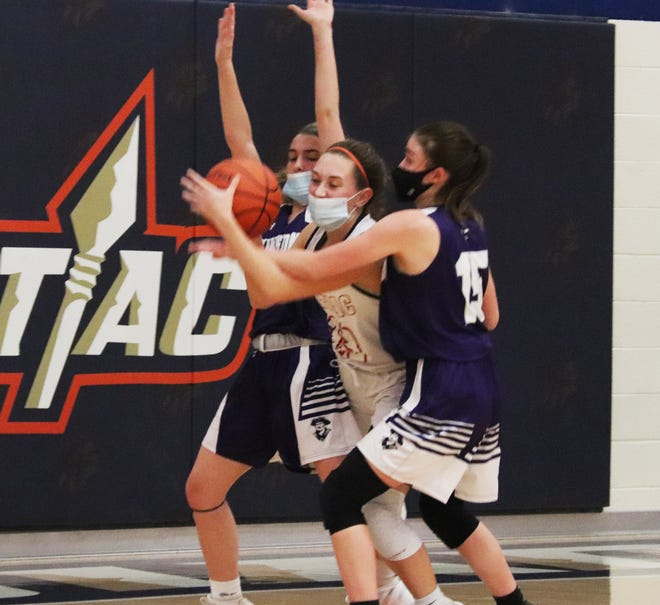Pontiac's Addison Masching tries to squeeze between Lexington defenders Lily Woith, left, and Emma Boyd Tuesday night. Masching scored a game-high 27 points to lead the Indians past the Minutemen.